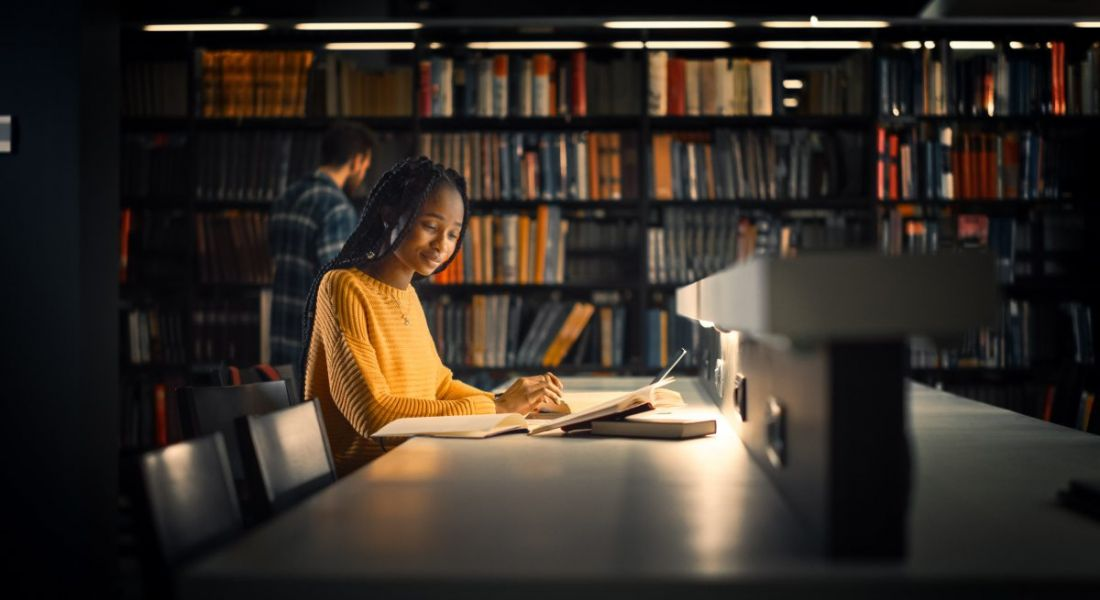 A young professional is sitting in a university library and working.