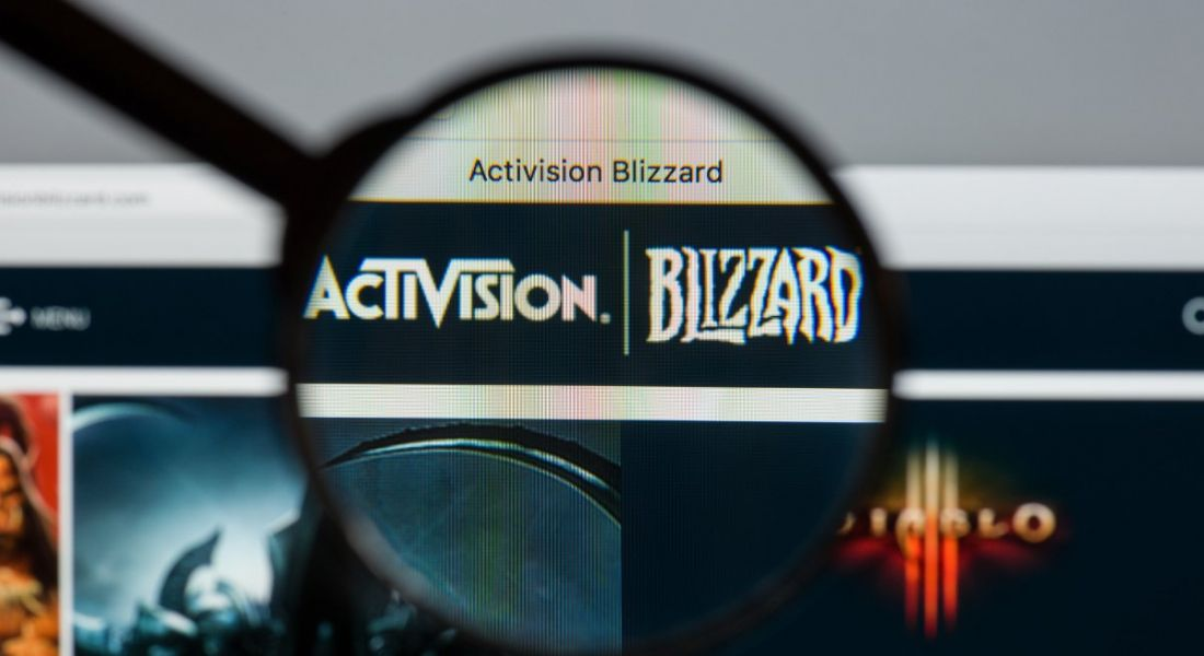 Activision Blizzard website homepage with logo under a magnifying glass.