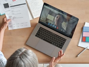 Two women are speaking to each other over a video call during a remote job interview.