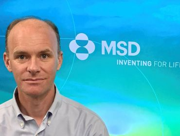 Barry Kennedy, automation engineer at MSD, is smiling into the camera in front of a screen with the company logo.