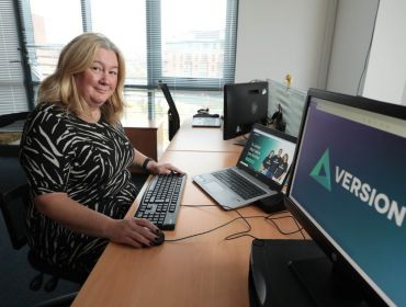 Version 1 Northern Ireland director of operations Lorna McAdoo is sitting at a desk in front of a computer with the company logo on the screen.