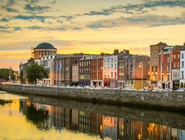 A view of the quays in Dublin city. The River Liffey is in the foreground and a long line of buildings is in the background against an orange sunset sky.