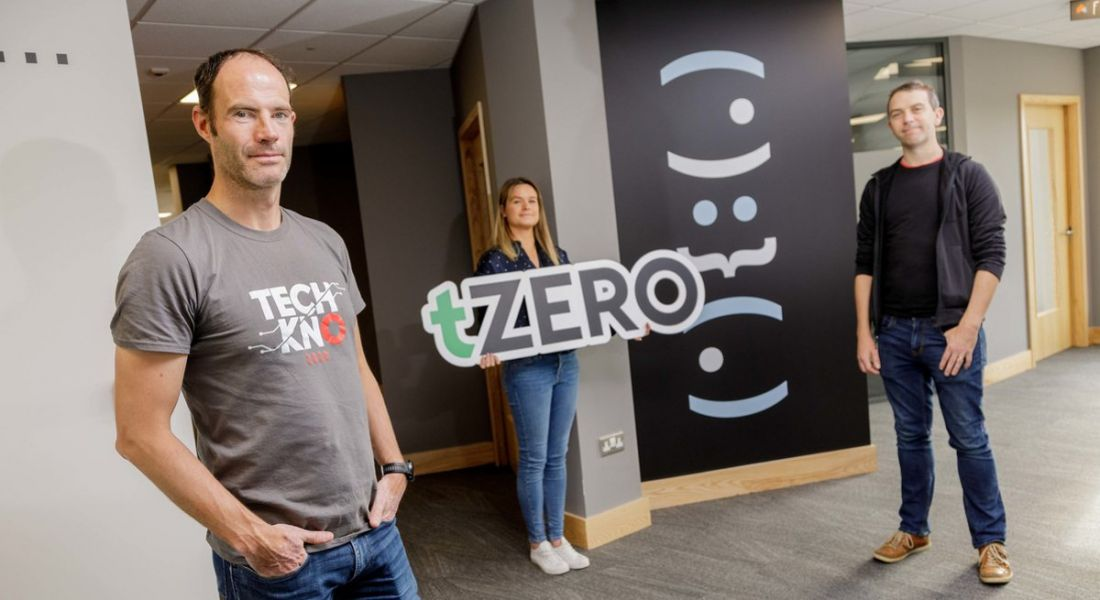 Senior employees at Overstock are standing in an office setting and smiling into the camera. One is holding up a tZero sign.