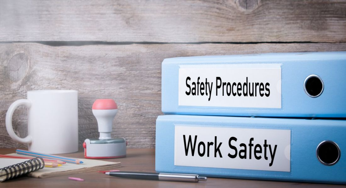 Two binders are sitting on a desk beside a cup of coffee. One binder has a label that reads 'Work Safety', the other says 'Safety Procedures'.