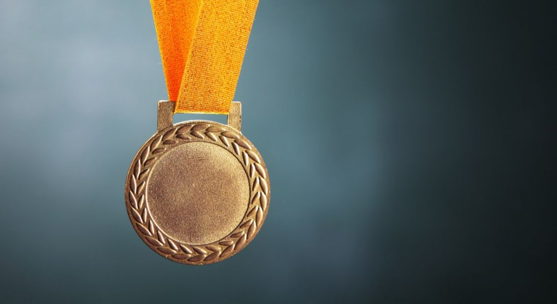 A gold medal with a yellow strap is handing against a dark green background.
