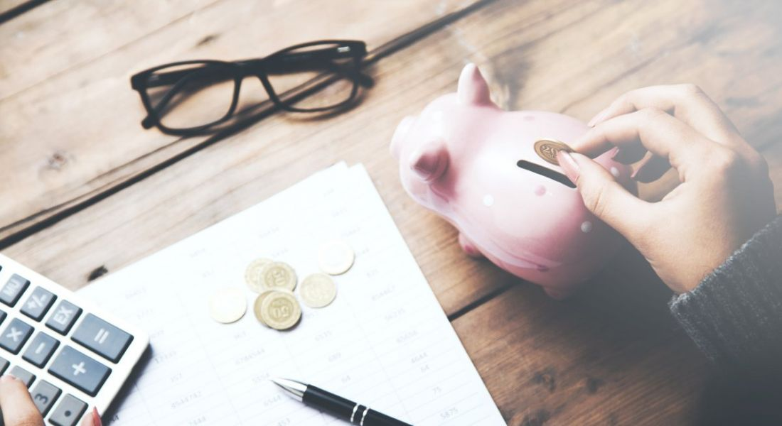 A person is putting a coin into a piggy bank beside glasses and a calculator on a wooden desk.