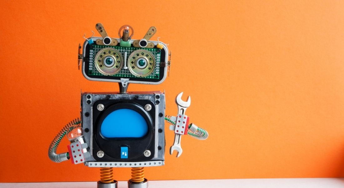 A cute toy robot is holding a spanner and standing against an orange background, symbolising automation.