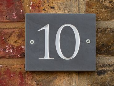 A slate number 10 sign against an old red-brick wall.