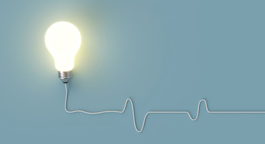A lightbulb is lit up against a pale blue background.
