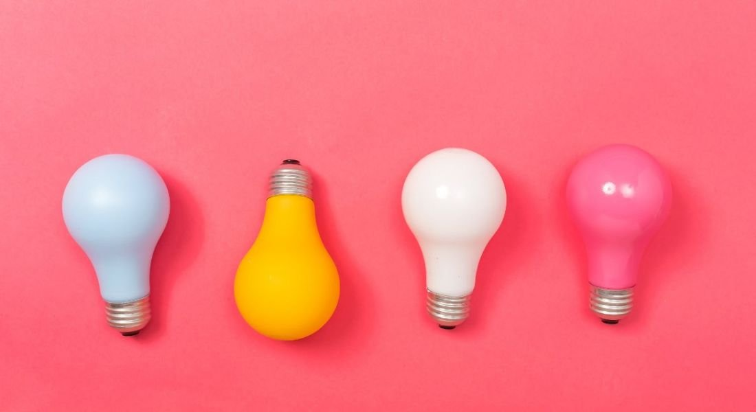 Four multi-coloured lightbulbs against a bright pink background, symbolising work in STEM.