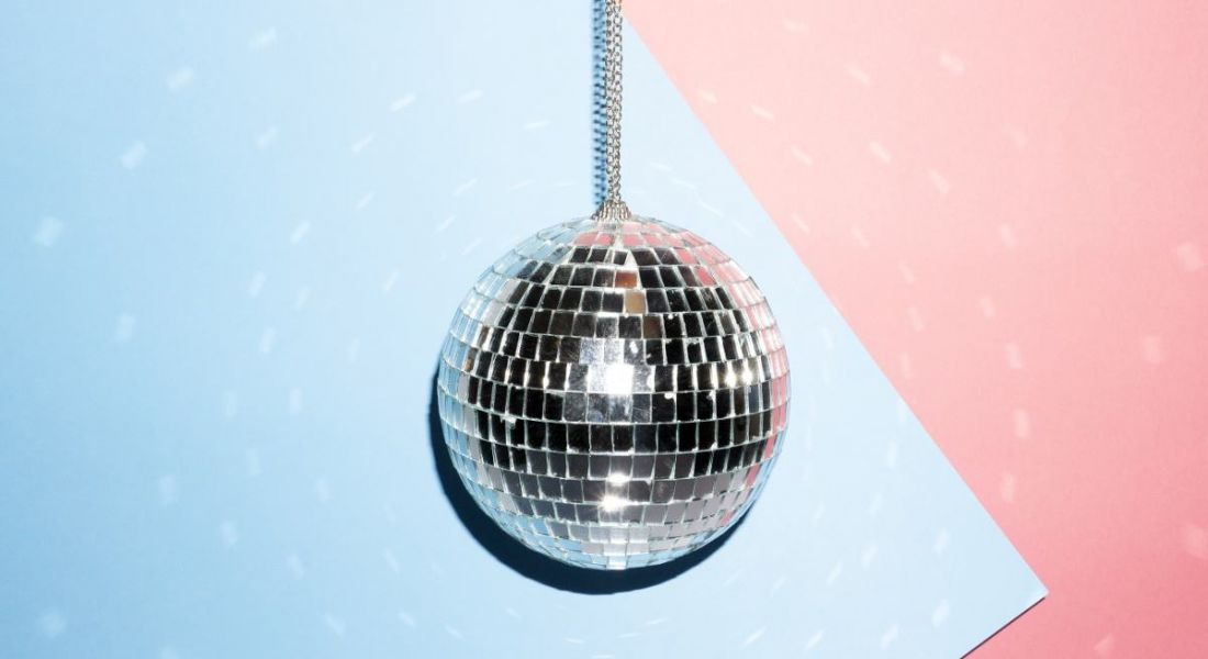 A silver disco ball is hanging against a blue and pink background, symbolising stepping off the dancefloor for self-reflection.