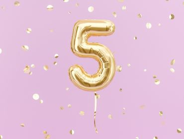 Gold foil balloon in the shape of a number five against a bright pink background.