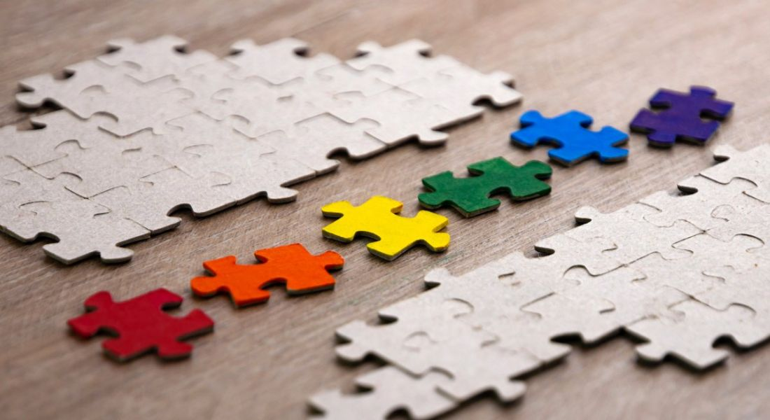 Colourful puzzle pieces are lined up on a wooden table, symbolising a diverse talent pipeline.