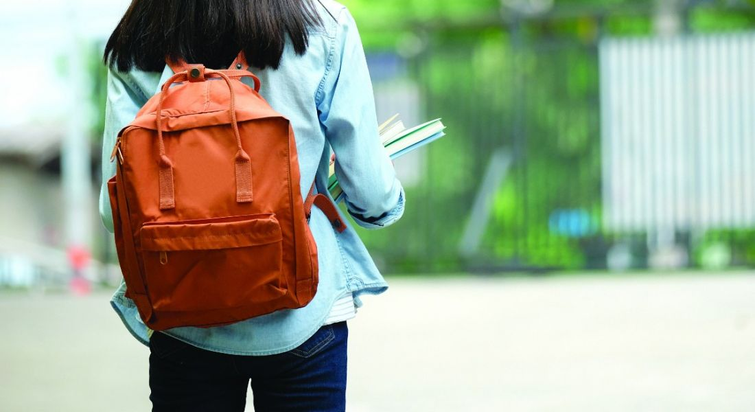 A student is facing away from the camera wearing an orange backpack and carrying books in an outdoor setting.