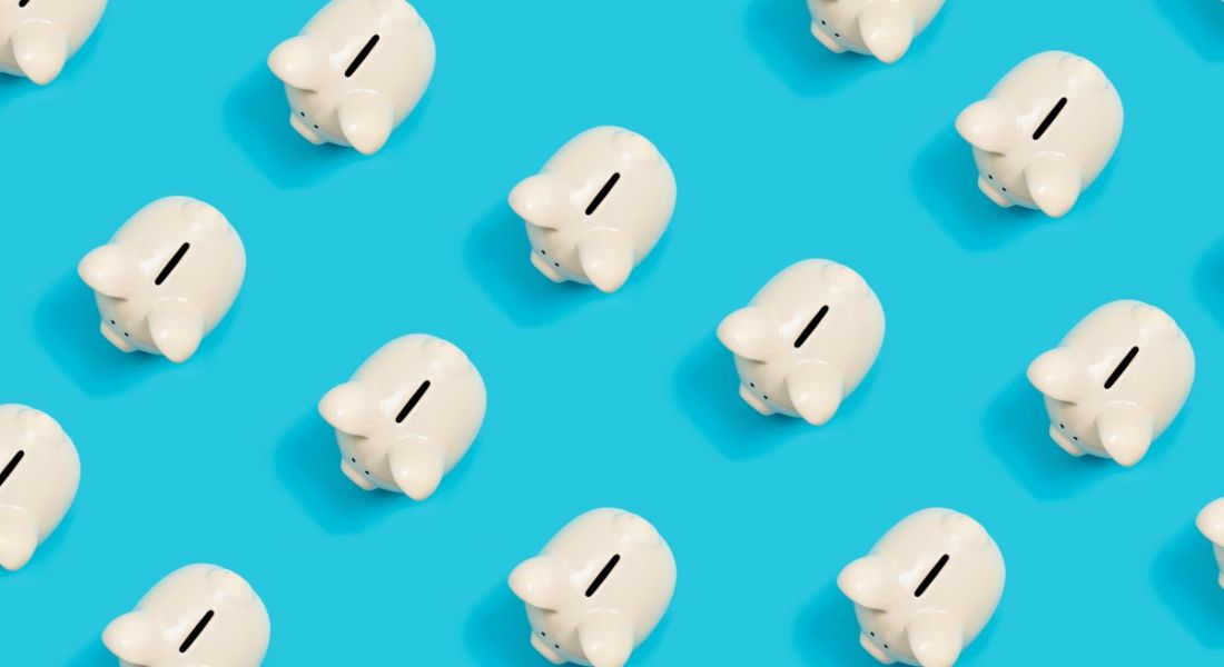 Many white piggy banks on a blue background, symbolising a career in fintech.