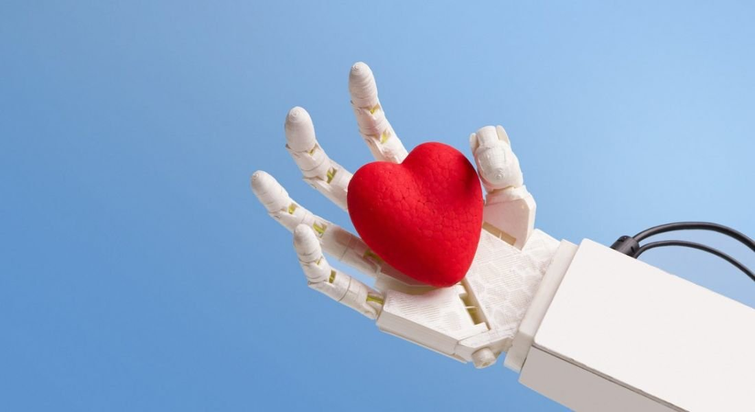 A white robot hand is holding a red heart against a blue background.