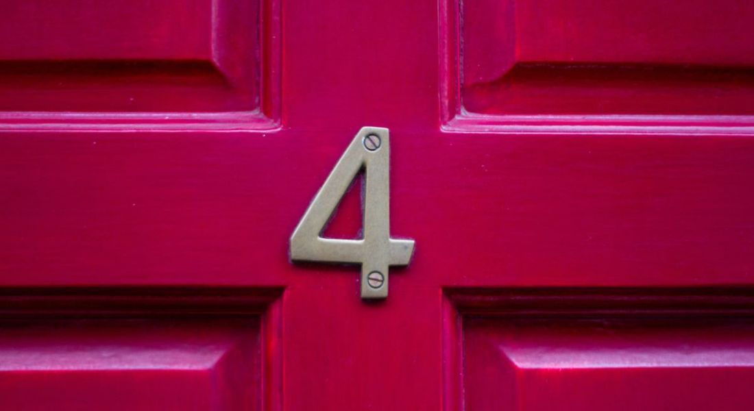 A red front door with a metal number four on it.