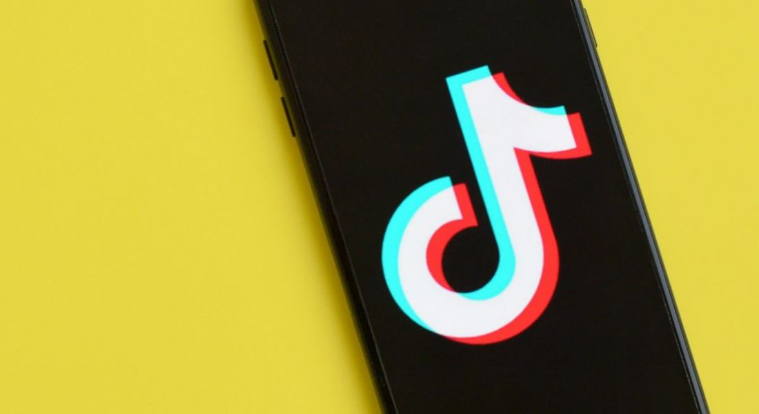 A phone displaying the TikTok logo on a sunny yellow background.