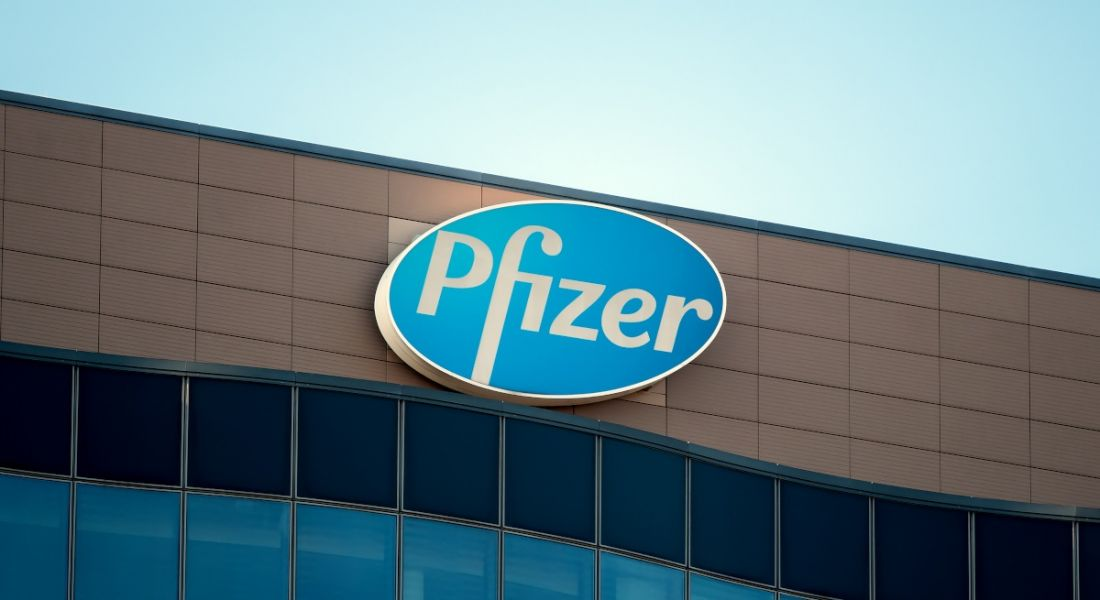 The blue and white Pfizer logo at the top of an office building against a clear, blue sky.