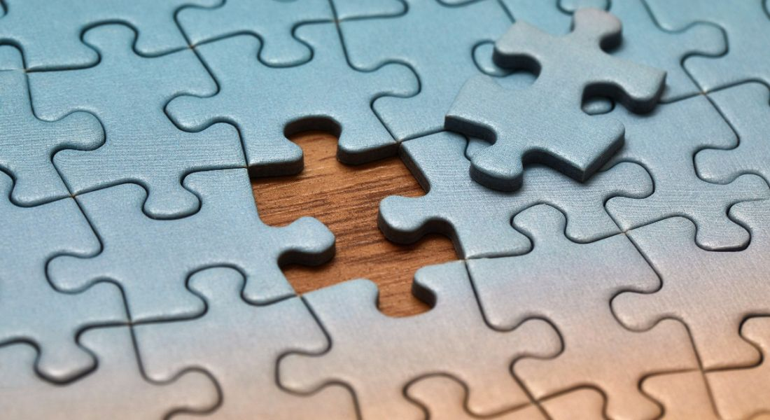 Blue jigsaw puzzle on a wooden table with one last piece missing, symbolising a skills gap.