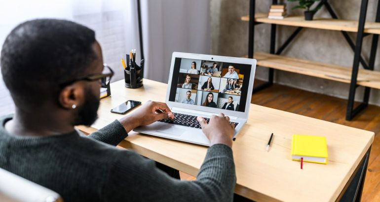 A young professional is starting a new job remotely, talking to his new colleagues on a video call.