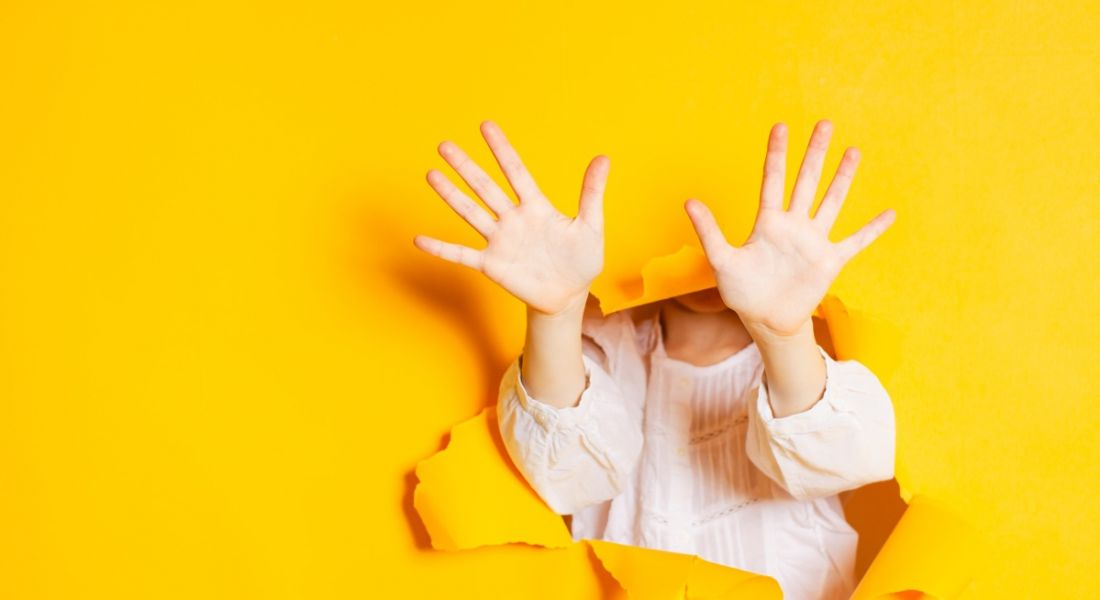 A girl is pushing through a yellow background and holding her 10 fingers up.