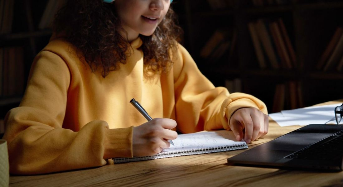 A student is wearing a yellow jumper and working with a laptop and notebook on a wooden desk.