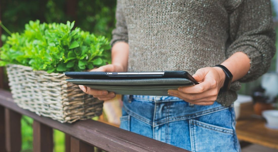 Woman in a light brown knitted jumper beside a flowerpot and holding a tablet device.