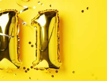 Gold foil balloons in the shape of the number 11 are against a bright yellow background with confetti.