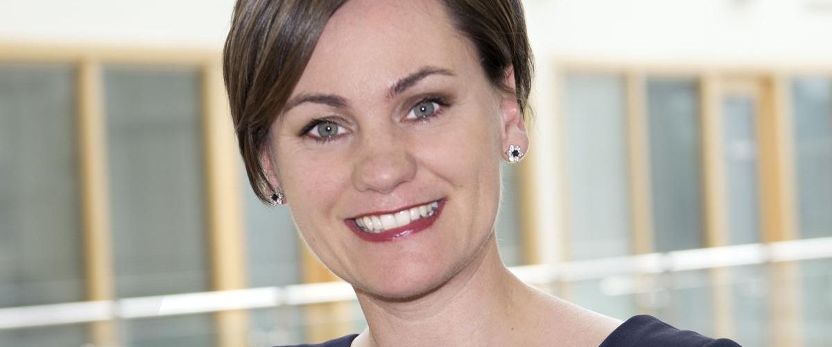 A headshot of Sarah McDonough standing in an office space.