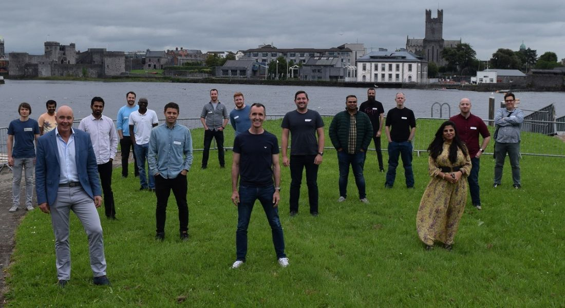 Some of the Transact Campus team standing socially distant from one another on grass with Limerick city behind them.