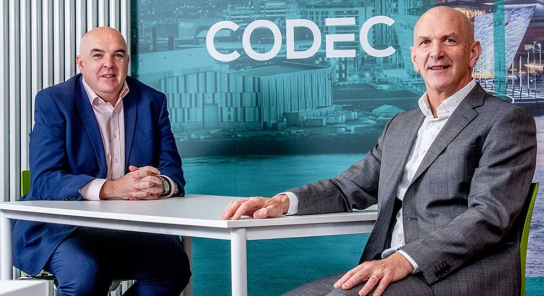 John Molloy of Codec and George McKinney of Invest Northern Ireland are sitting at a desk in suits with Codec branding behind them.