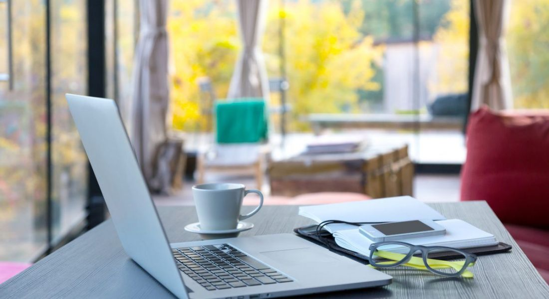 A laptop sits on a table with a notepad, a coffee cup and a pair of glasses. In the background, the room has large windows with colourful trees outside.