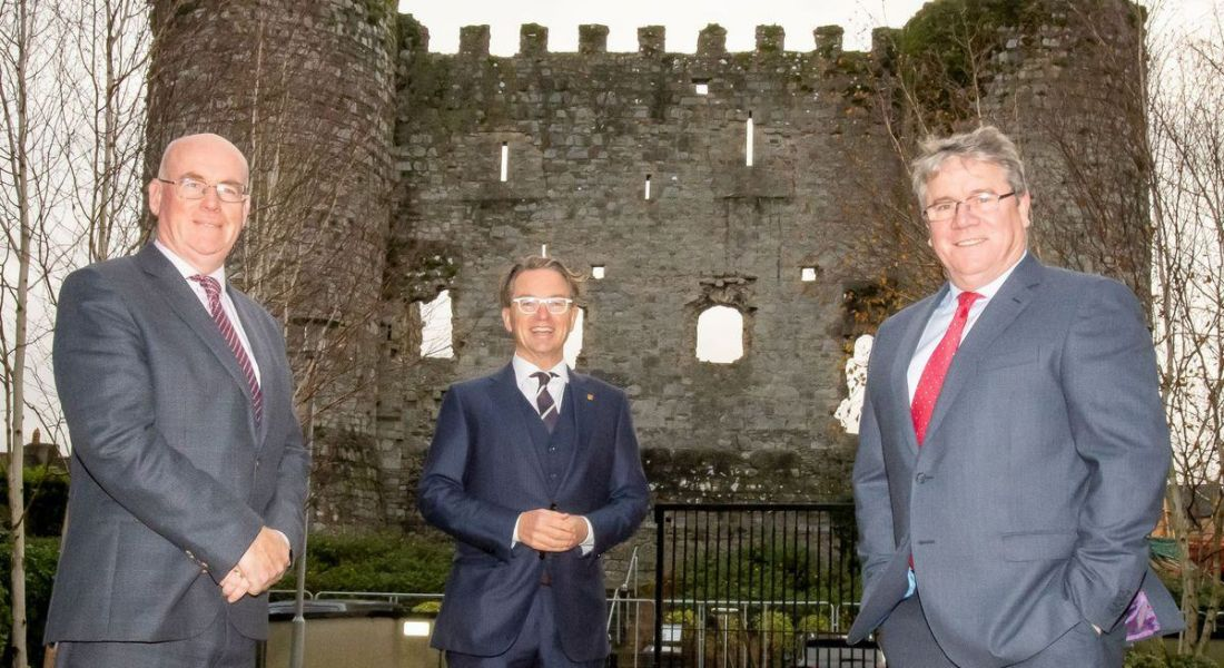 Three men in suits are standing in front of a castle ruin for the launch of HaloCare.