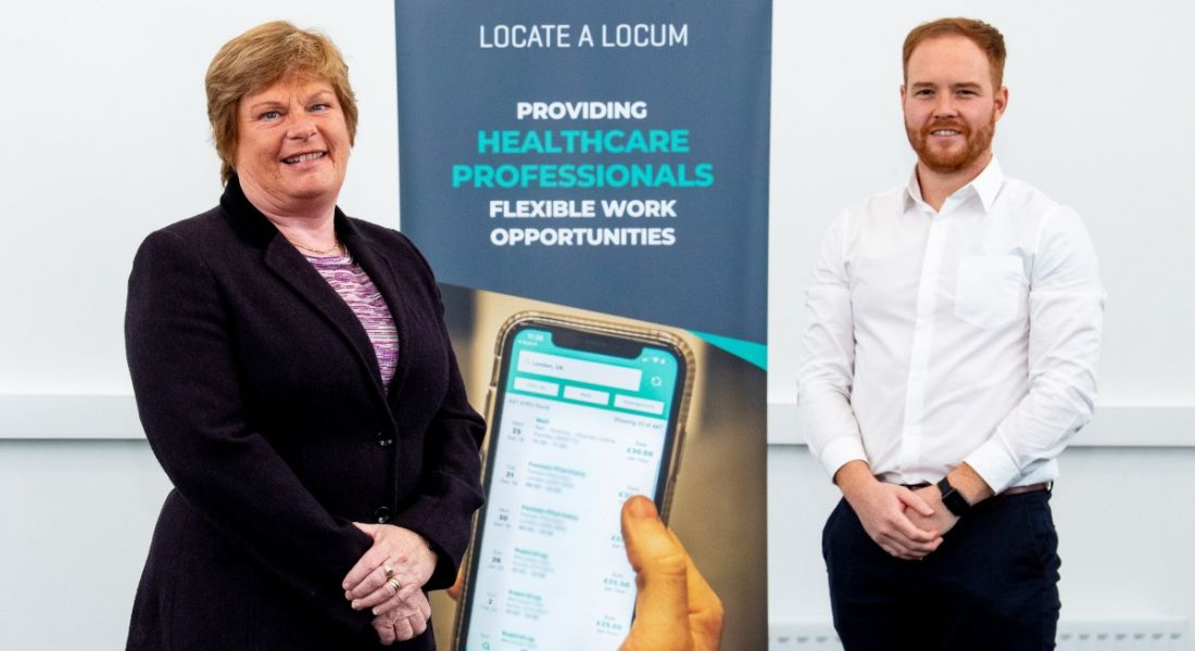 A woman and a man stand either side of a Locate a Locum pop-up banner, both standing with their hands clasped in front of their bodies.