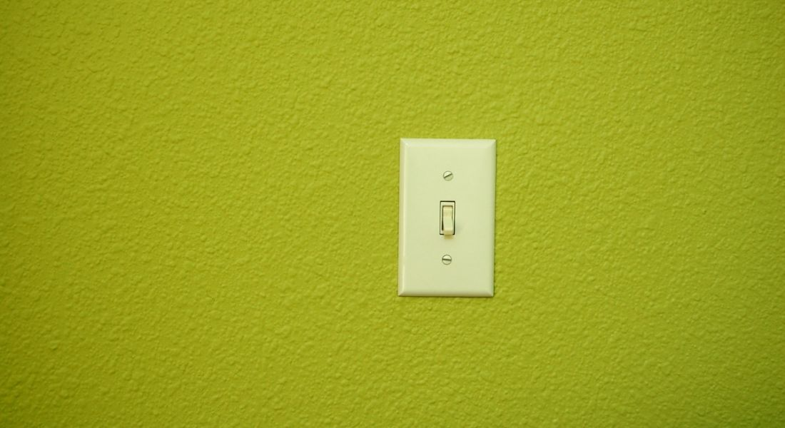 A light switch on a bright green wall.