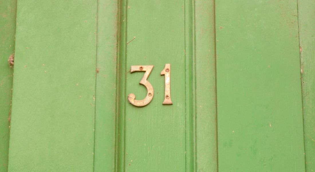 The number 31 in gold against a bright green front door.