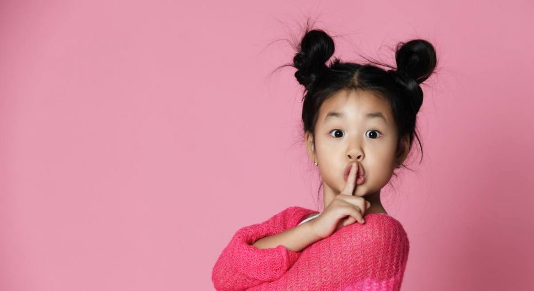 A cute young girl is wearing a pink jumper against a pink background and holding her finger to her lips.