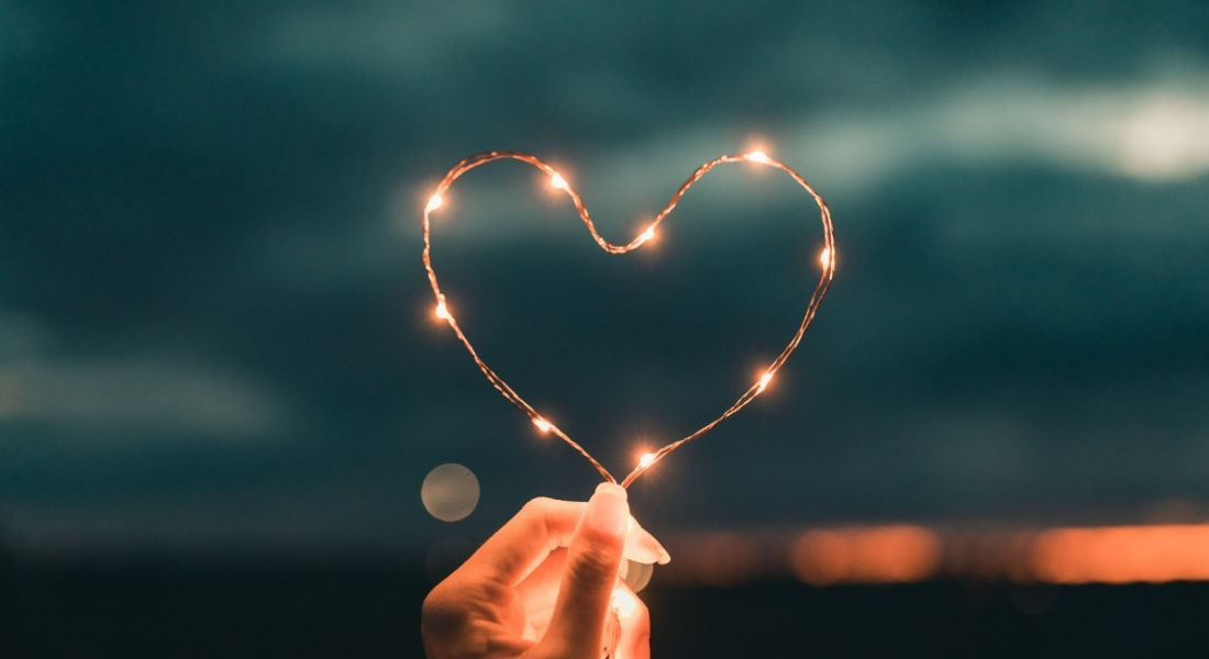 A person's hand is holding fairy lights in the shape of a heart at night.