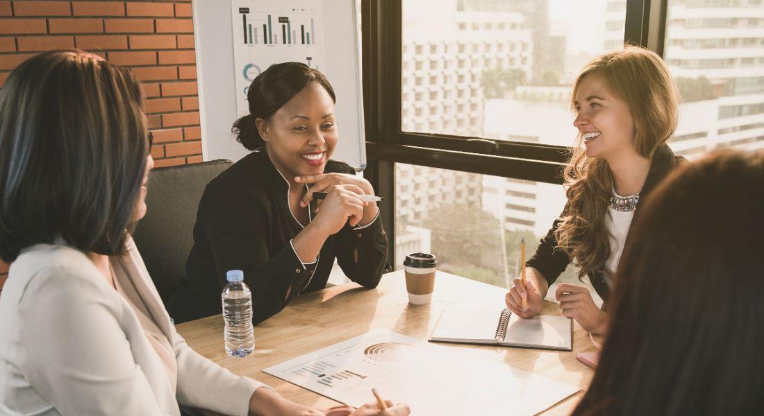 Women in leadership are sitting by a window in a boardroom.