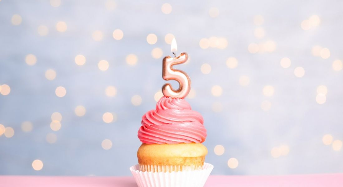 Birthday cupcake with number five candle on table against festive lights with pink icing.