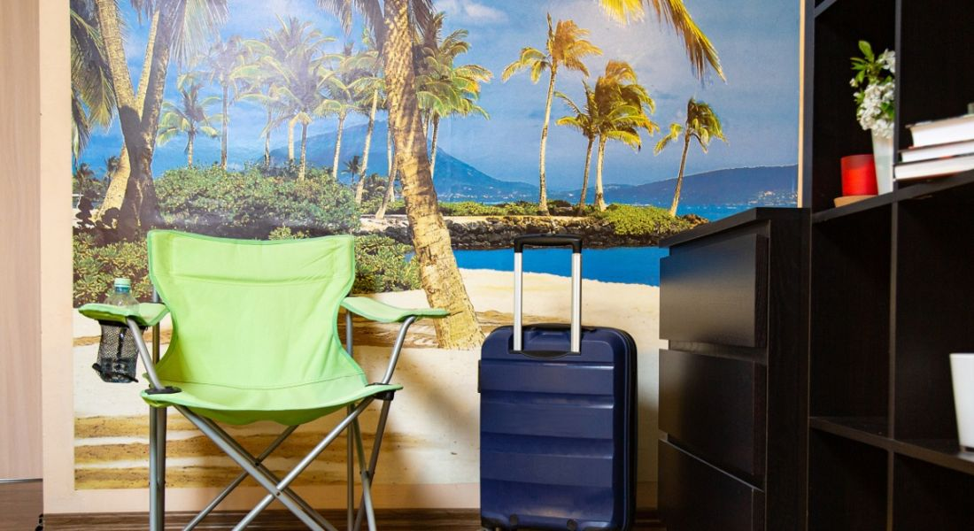 A green chair in an office is in front of a poster of a beach, symbolising a fake Zoom background.