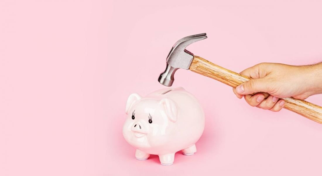 A hand is holding a hammer close to a pink piggy bank against a pink background.
