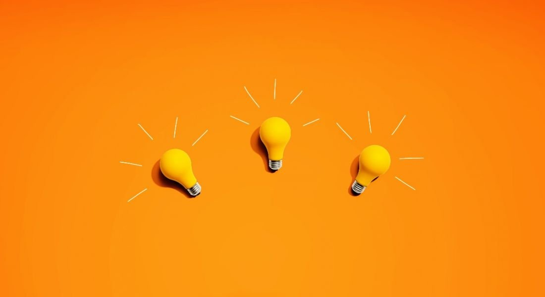 Three yellow lightbulbs are laying against a bright orange background.
