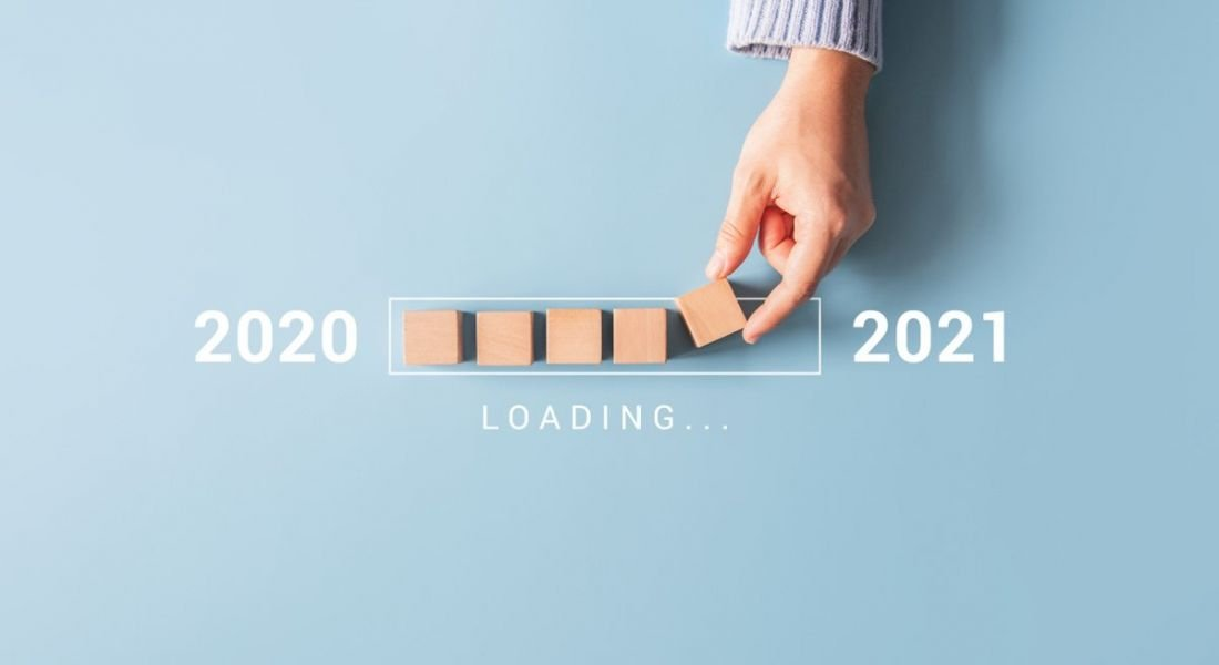 A person's hand is placing wooden blocks in a loading bar shape, moving from 2020 to 2021.