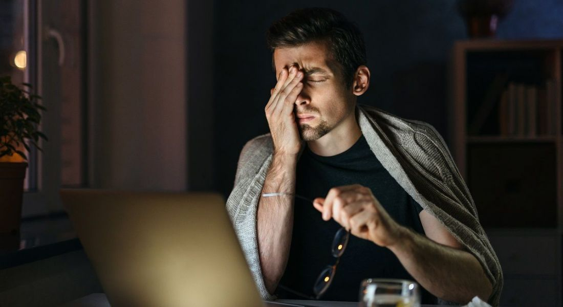 Exhausted man rubbing his eyes while looking at his laptop in a dark room.