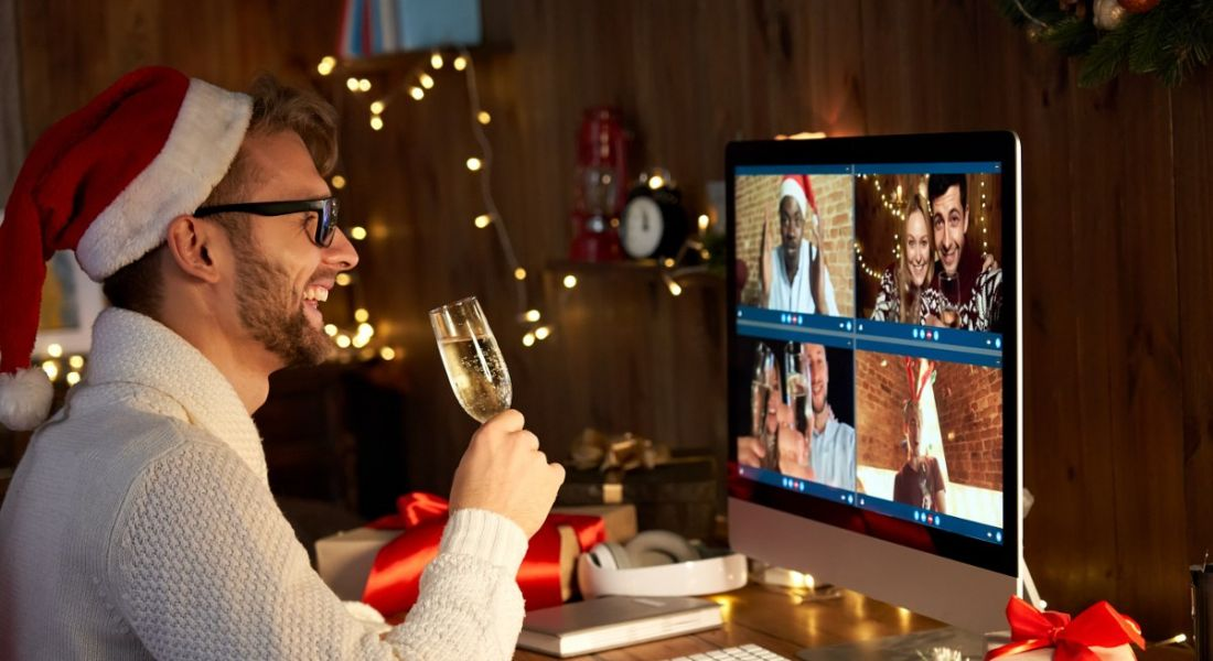 A man is drinking champagne and talking to colleagues on a video call at a virtual Christmas party.