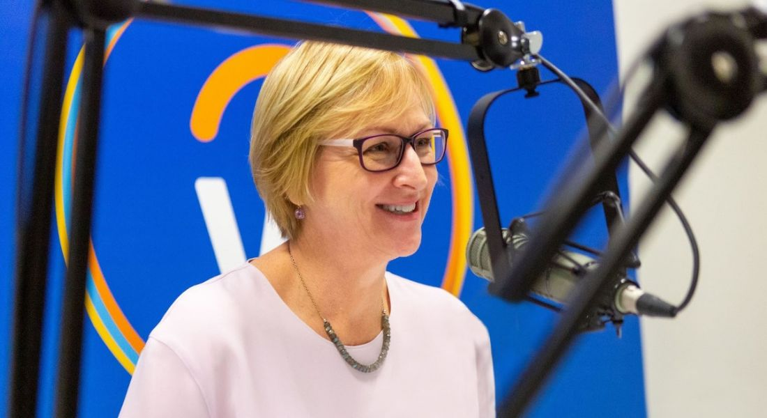 Workday's Chris Byrne sits at a microphone recording a podcast. The Workday logo is on a screen behind her.