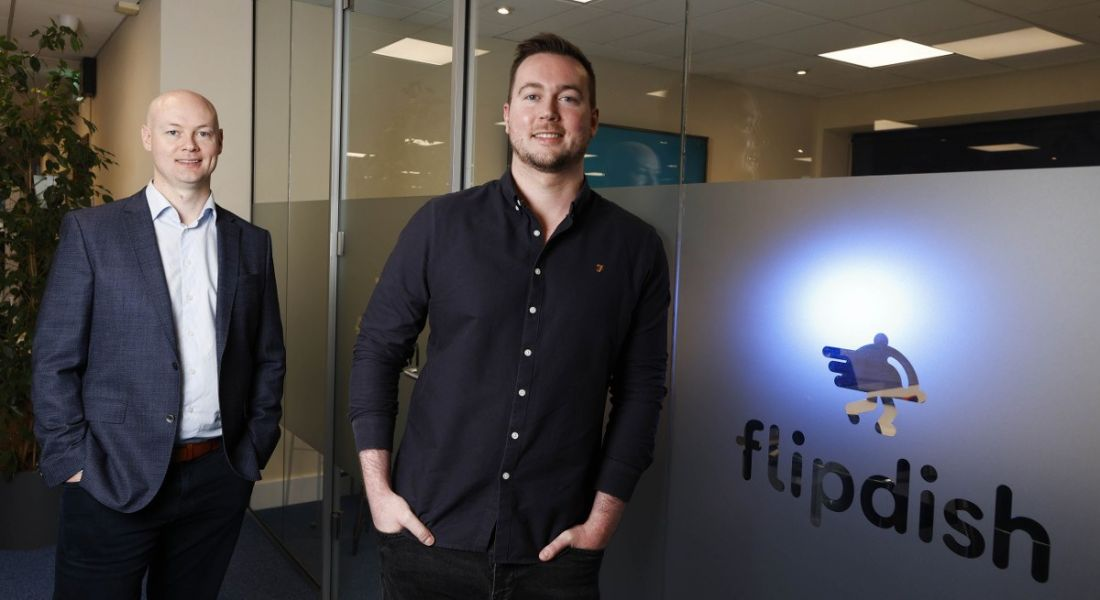 Conor and James McCarthy of Flipdish are standing in an office that has the Flipdish logo on a glass wall beside them. They are smiling into the camera.