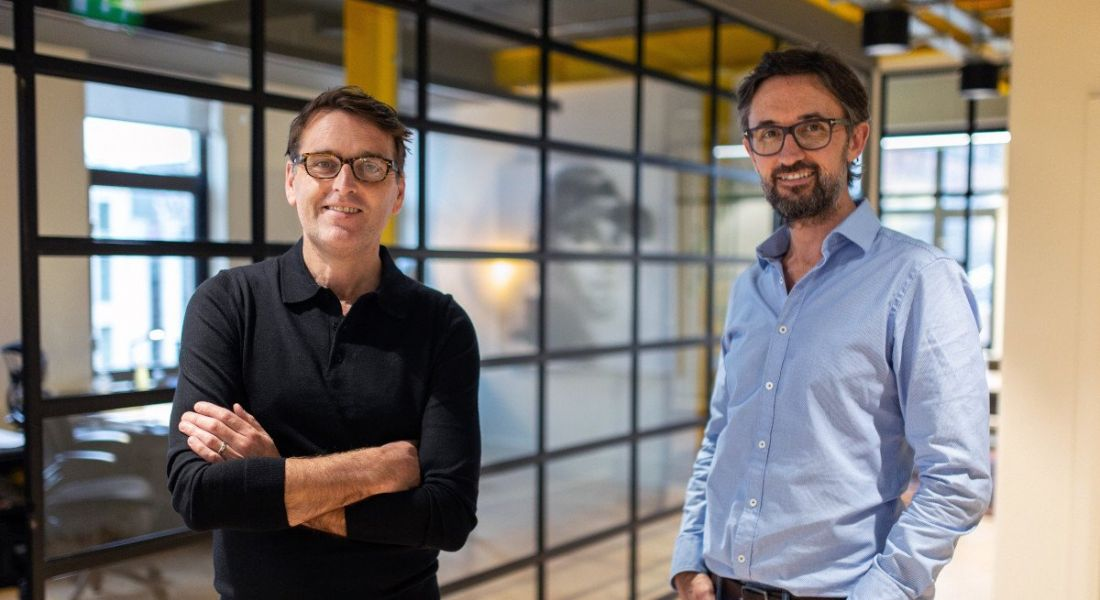 Mammoth co-founders Paul Martin and Jeremy Poots, wearing business-casual attire, stand in a brightly lit office space.